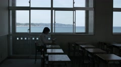 Japanese high-school student with book in an empty classroom Stock Footage