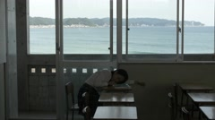 Japanese high-school student sleeping in an empty classroom - stock footage