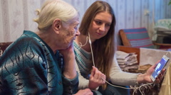 the grandmother and the granddaughter talk by video conference to relatives. - stock footage