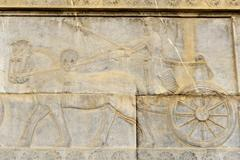 Ancient relief of Achaemenid Persian driving a carriage Apadana Palace - stock photo