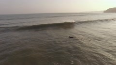 Aerial footage of surfer in the ocean at sunset, Chiba Prefecture, Japan Stock Footage