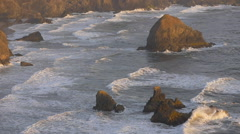 Sunset slow motion wave breaking on Oregon coastal rocks Stock Footage