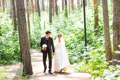 Happy bride and groom walking in summer forest. Young wedding couple Stock Photos