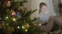 Young girl sitting with a laptop near a Christmas tree - stock footage