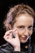 curly young woman in jacket and sunglasses - stock photo