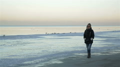Lone sad beautiful girl walking along the shore of the frozen sea on a cold day Stock Footage
