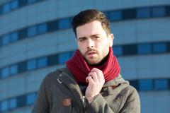 Male fashion model posing outdoors with jacket and scarf Stock Photos