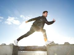 Portrait of male fashion model balancing with legs open - stock photo