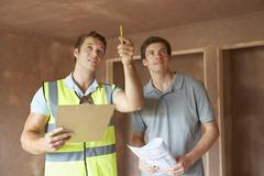 Builder And Inspector Looking At New Property - stock photo