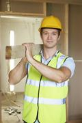 Builder Carrying Timer On Building Site - stock photo