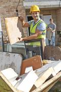 Stock Photo of Builder Putting Waste Into Rubbish Skip