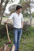 Man with axe and firewood - stock photo