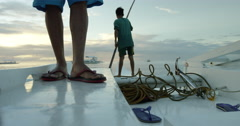 Philippines - Boy pushing out boat into the water in the morning Stock Footage