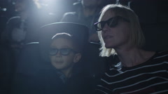 Family with child are having fun while watching 5d film screening in cinema - stock footage