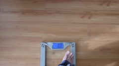 A man steps on scale to weigh himself Stock Footage