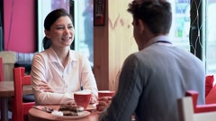 Two people in cafe laughing and talking Stock Footage