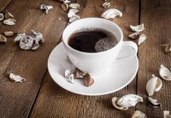 Cup of coffee on wooden background, decorated dried aromatic parts of plants - stock photo