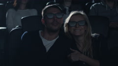 Couple embrace each other while having fun watching 5d film screening in cinema - stock footage