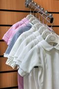 Collection of jumpsuits baby clothes on hangers in store closeup Stock Photos