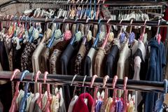 Collection fashion clothing on hangers at the showroom closeup - stock photo
