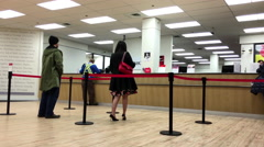 People at service counter talking to the teller inside HSBC Bank - stock footage