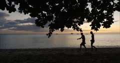 Philippines - Sunset on the beach. A couple walking by in silhouette. Stock Footage