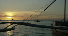 Philippines - Fisherman in canoe floating into sunset Stock Footage