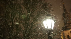 Warm Glow of Street Light Surrounded by Snowflakes in First Snowfall of the Stock Footage