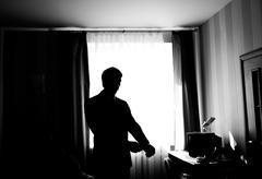 Stock Photo of Wearing his favorite shirt. Silhouette of man buttoning   shirt