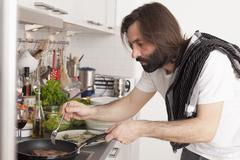 Mid adult man preparing meat in domestic kitchen Stock Photos