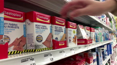 People taking Elastoplast heavy fabric robuste inside Shoppers drug mart store Stock Footage