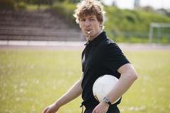 Referee blowing whistle while carrying soccer ball on field Stock Photos