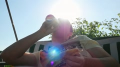 Fat man drinking beer and eating a fish in the garden on swing in slowmotion at - stock footage