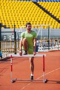 Full length of track and field athlete warming up on hurdle at sports track Stock Photos