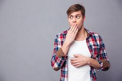 Amazed astonished man covered mouth by hand and feeling afraid Stock Photos