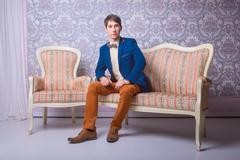 Young man in classic suit is sitting on the couch Stock Photos