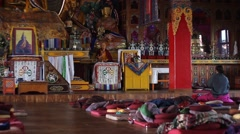 Woman sitting in the meditation hall of the Kopan monastery Stock Footage