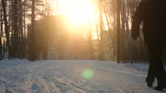 Man Takes a Walk Through Beautiful Snowy Forest Scene with Sun Setting behind - stock footage