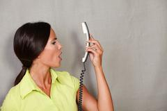 Long hair lady with hair back holding phone dissatisfied and screaming on gre - stock photo