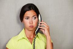 Customer service lady weary while holding phone and looking away against grey - stock photo