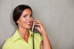 Charismatic woman smiling a toothy smile while talking on the phone and looki - stock photo