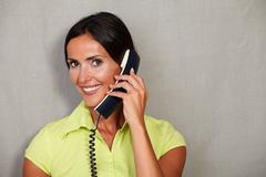 Stock Photo of Long hair female with toothy smile while holding phone and looking at camera