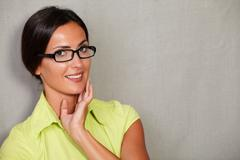 Toothy smiling lady with glasses and hand on face while contemplating and loo - stock photo