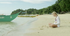 Philippines - Girl sitting on the beach looking out the water. Stock Footage