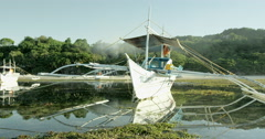 Philippines - Local fisher boat Banca with beach and djungle in background Stock Footage
