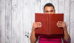 Handsome man hiding behind register or journal in studio - stock photo