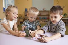 Children playing with animal toys at table in classroom Stock Photos