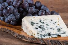 French roquefort cheese with black grapes Stock Photos