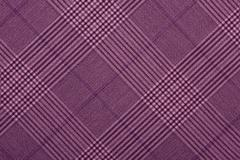 Purple material in geometric patterns, a background - stock photo