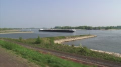 Vehicle shot from river dike - inland ship downstream on river Waal Stock Footage